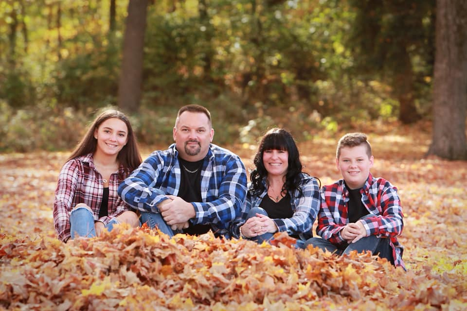 a family sitting in leaves